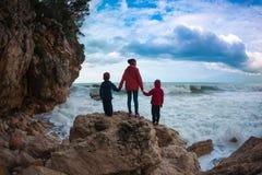 妇女的剪影和孩子反对海和天空 免版税库存照片