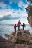 妇女的剪影和孩子反对海和天空 库存图片