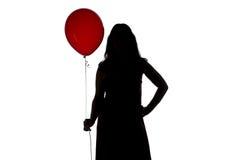 妇女的剪影照片与红色气球的 免版税库存照片