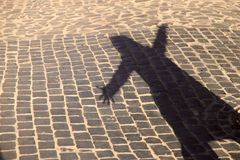 妇女的剪影的奇怪的阴影在一条老石路的 黑阴影,女性手 免版税库存照片
