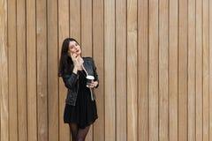 妇女的半身画象谈话在巧妙的电话,当站立与时拿走咖啡对有拷贝空间的墙壁, 库存图片