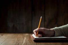 妇女的在纸的手文字特写镜头  免版税库存照片