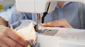 妇女的工作在一台缝纫机的手裁缝的特写镜头在她的演播室 股票视频