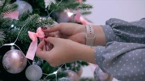 妇女的年轻手传播在圣诞树的一把弓,装饰与欢乐光的欢乐圣诞树和 股票录像