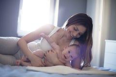 妇女的幸福是她在胳膊保留她的婴孩 免版税库存照片