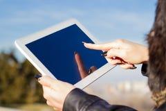 妇女的手举行和感人的数字式片剂个人计算机 库存图片