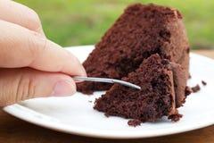 妇女的手举行对切片的一把叉子巧克力蛋糕 免版税库存照片