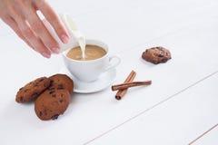 妇女的手倒牛奶入咖啡 免版税图库摄影