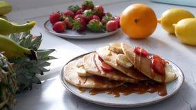 妇女的手倾倒在薄煎饼之上的浓缩牛奶与stawberry 影视素材