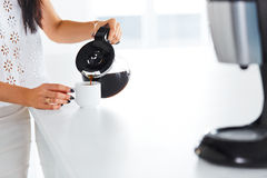 妇女的手倾吐的咖啡到咖啡杯 免版税库存照片