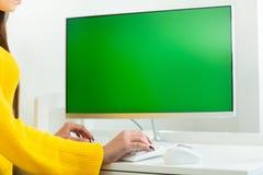 妇女的手关闭,工作在有绿色屏幕的计算机,在办公室环境里 免版税库存照片