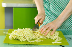妇女的手切了在绿色黑板的圆白菜 免版税库存图片
