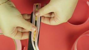 妇女的手包裹在模板的一条桃红色丝带做的礼物弓 红色背景 股票视频