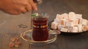 妇女的手在传统玻璃杯子把土耳其茶放在木桌上 ?? 影视素材