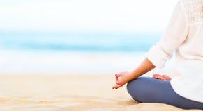 妇女的手在海滩实践瑜伽并且思考 库存图片