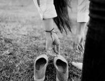 妇女的手垂悬在帆布鞋 库存照片