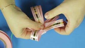 妇女的手塑造一把桃红色丝带礼物弓的瓣 背景看板卡祝贺邀请 股票录像