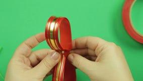 妇女的手塑造做的礼物弓空白的红色丝带 绿色背景 股票录像