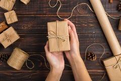 妇女的手拿着工艺纸礼物  以干桔子为背景,桂香,杉木锥体,在一张木桌上的茴香 免版税库存照片
