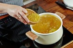 妇女的手拿着木碗以未加工的面条放它入煮沸的肉汤 在黑火炉的被打开的白色平底深锅 免版税库存照片