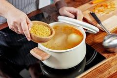 妇女的手拿着木碗以未加工的面条放它入煮沸的肉汤 在黑火炉的被打开的白色平底深锅 库存图片