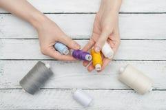 妇女的手拿着缝合的色的螺纹 免版税库存照片