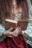 妇女的手拿着老葡萄酒书的中世纪礼服的 免版税库存照片