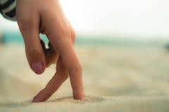 妇女的手指在沙子走在海滩 库存图片