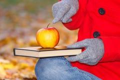 妇女的手指显示书的和苹果在秋天停放 免版税库存图片