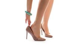 妇女的手接触脚跟鞋子 库存照片