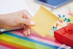 妇女的手有空白的黏着性笔记的 免版税库存照片