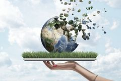 妇女的手有绿草的藏品片剂侧视图在屏幕和地球地球上在溶化的上面 免版税库存图片