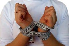 妇女的手栓了与一卷测量的磁带 免版税库存图片