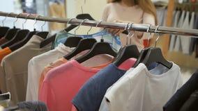 妇女的手特写镜头偷窃了与衣裳的挂衣架 垂悬在一个挂衣架的明亮的夏天衣裳在商店 影视素材