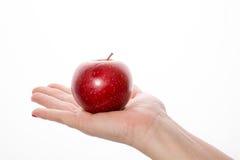 妇女的手用在白色背景的红色苹果 免版税库存照片