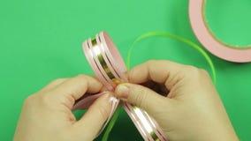 妇女的手绑住与桃红色丝带空白一条绿色丝带一把礼物弓的在绿色背景 股票录像
