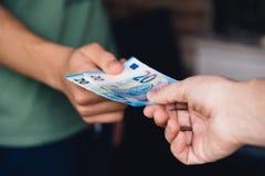 妇女的手给一个年轻人捐欧洲钱 免版税库存图片
