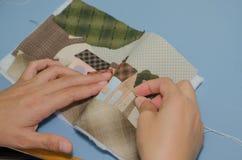妇女的手缝合的被子 库存照片