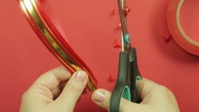 妇女的手节约红色丝带空白的与一把剪刀的做的礼物弓 红色背景 股票视频