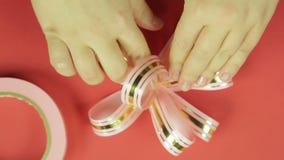 妇女的手调直一把桃红色丝带礼物弓的瓣并且给它弓的形状 红色背景 股票视频