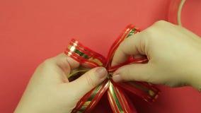 妇女的手调直一把桃红色丝带礼物弓的瓣 红色背景 影视素材