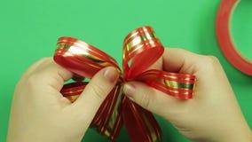 妇女的手调直一把红色丝带礼物弓的瓣并且给它形状 绿色背景 股票视频