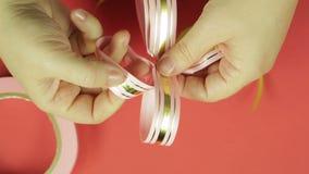 妇女的手调直礼物丝带弓的瓣从桃红色丝带的 红色背景 股票录像