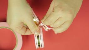 妇女的手调直礼物丝带弓的瓣从桃红色丝带的 红色背景 影视素材