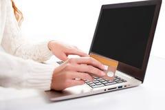 妇女的手输入数据使用膝上型计算机和拿着信用卡  免版税库存图片