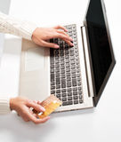 妇女的手输入数据使用膝上型计算机和拿着信用卡  免版税库存照片