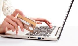 妇女的手输入数据使用膝上型计算机和拿着信用卡  库存图片
