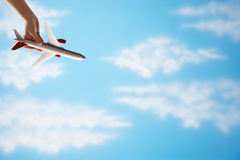 妇女的手飞行颠倒玩具飞机特写镜头反对多云天空 库存图片