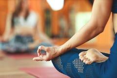 妇女的手,mudra,实践的瑜伽思考在莲花坐 免版税库存照片