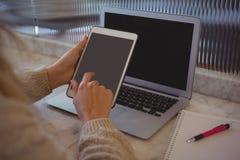 妇女的播种的手有片剂和膝上型计算机的在咖啡馆 库存照片